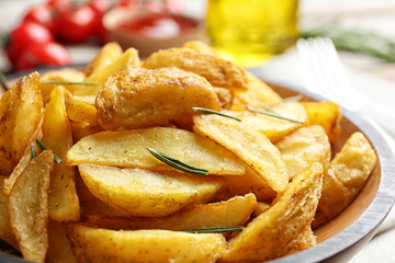 Plate with tasty baked potato wedges on table, closeup