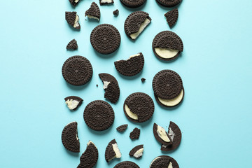 Tasty chocolate cookies with cream on color background, flat lay
