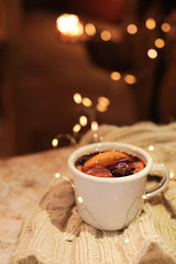 Cup of hot mulled wine and garland on table against blurred background. Space for text