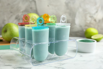 Spirulina popsicles in ice cream mold on marble table