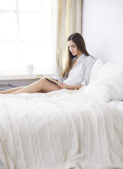 Portrait of woman using tablet and drinking coffee while sitting on the bed in the morning