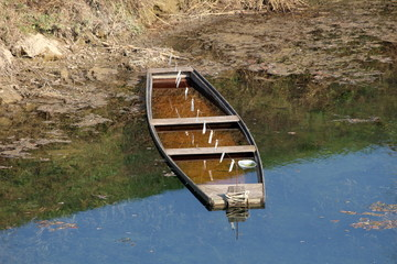 Partially submerged old wooden river boat next to muddy river bank surrounded with floating grass and clear water on warm sunny day