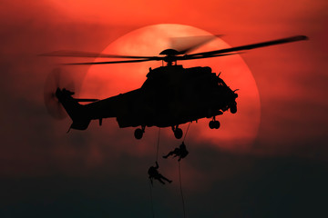 Poster Helicopter Shot of rescue helicopter hopping in front of the big sun with two soldiers rappelling from high