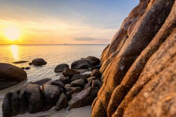 Wall Mural - Sea sunset rocks beach on blue sky background. Beauty evening sunrise. Blue background. wonderful landscape