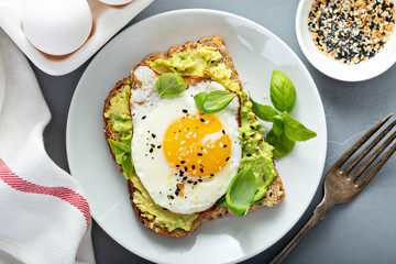 Avocado toast with fried sunny side up egg overhead view