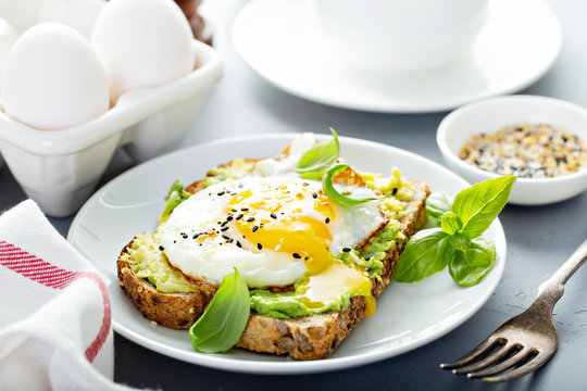 Avocado toast with fried sunny side up egg with runny yolk