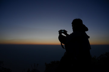 Photographer Taking Pictures On Mountain view with silhouette sunrise.