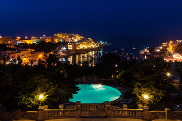 View of St. George's Bay seafront lights by night, with a blue luxury swimming pool and boats and yachts anchored. St Julian's or San Giljan, Central Region, Malta. Evening in Paceville district.