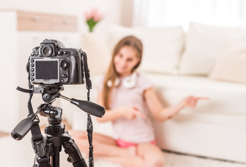 Young teen girl blogger on camera screen