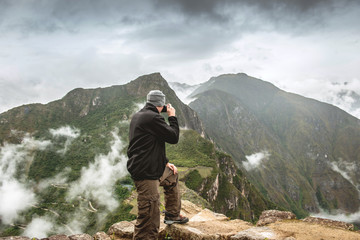 Standing man taking pictures of Machu Picchu