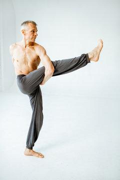 Senior athletic man with naked torso practising yoga poses in the white studio