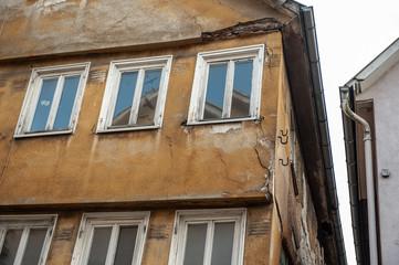 Mittelalter Altbau mit bröckelndem Hausputz und Spiegelungen in den Fenstern