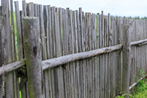 A Scratched Long Old Wooden Fence In A Village With Nails In