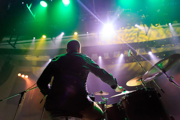 A back view of a band member playing drums  during a concert