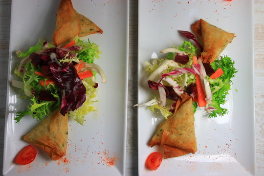 two plate of samoussa and lettuce salad, Asian cuisine