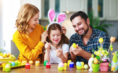 Happy easter! family mother, father and child daughter paint eggs for holiday