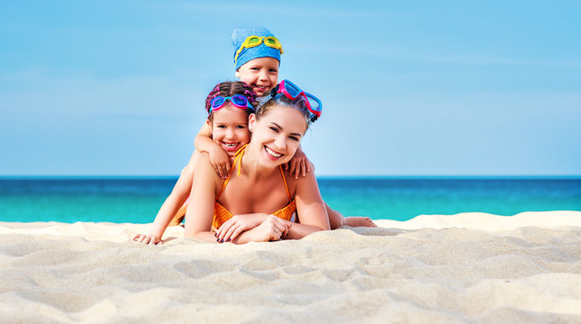 Happy family mother and chidren in masks on beach in summer.