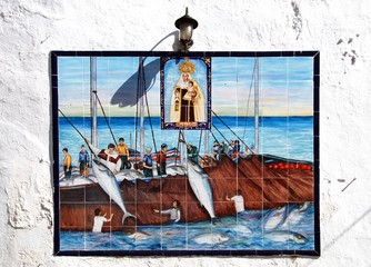 Traditional ceramic fishing picture with the fishermen being overlooked by Saint Catalina on a wall in the old town, Conil de la Frontera, Spain.