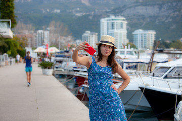 Young travelling woman in hat taking selfie photos over summer sunny mediterranean city