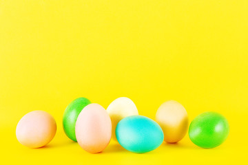 Bunch of blank painted Easter eggs of different pastel color isolated on bright yellow background with a lot of copy space for text. Front view, flat lay, close up.
