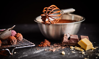 Chocolate coated whisk resting on mixing bowl