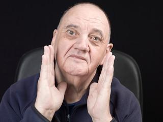portrait homme âgé dans son fauteuil de face isolé sur fond noir