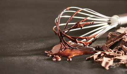 Melted dairy chocolate dripping off an old whisk