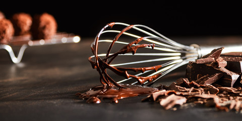 Old metal whisk coated in melted chocolate Wall mural