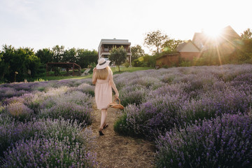 Pregnant girl blonde in a beige dress and straw hat. Lavender field. In anticipation of a child. The idea of a photo shoot. Walk at sunset. Future mom. Basket of flowers.