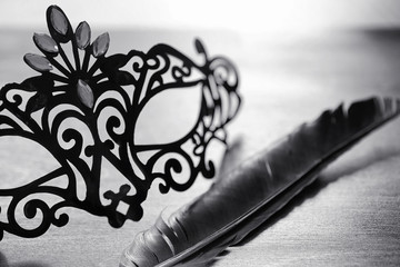 Carnival mask on the table. The subject of camouflage on a date during a carnival. Venetian mask on a wooden table in black and white.