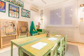 Kindergarten tables with painting brush. Art room for education children's creativity.