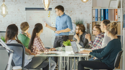 Man Makes Whiteboard Presentation to His Creative Office Staff. Coworkers Sit at the Big Glass Table with Open Laptops, Taking Notes. Modern Office is Stylish and Bright.