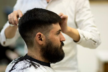 Bearded Man with black hair, having a haircut at a Chinese barbershop
