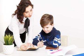 Female teacher helps teen boy to do his homework. Doing homework together