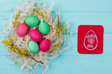 Traditionally painted Easter eggs in nest. Red paper card with drawn image of Easter egg. Easter greeting ideas for kids.