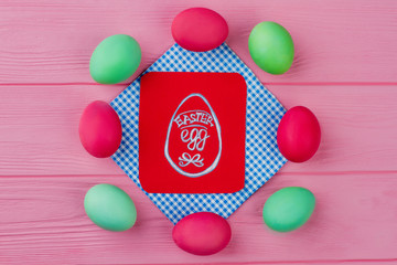 Red and green Easter eggs. Festive Easter composition from colored eggs on pink wood. Red card with picture of Easter egg. Symbols of Easter.