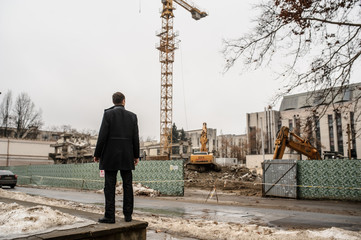 back view of a young man in a classic coat looking at a construction site