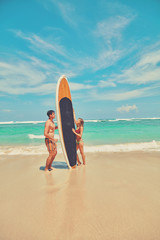 Couple with surfboard enjoying on the tropical beach.