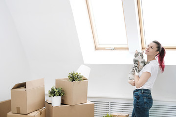 Young beautiful girl with colored hair in a white T-shirt and jeans, holding a pet cat and looking out the window against the background of cardboard boxes and things.