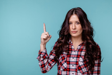 Photo of female person showing her finger up and smiling isolated over the blue backgrownd Wall mural