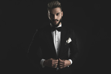 man in tuxedo adjusting his lounge jacket with both hands