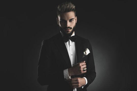 man in tuxedo fixing his sleeve