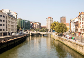 Bilbao, Spain-September 2018. River of the city with people in the shore. Describe the city life.