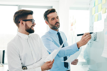 Two businessmen working together in modern office discussing new project on whiteboard