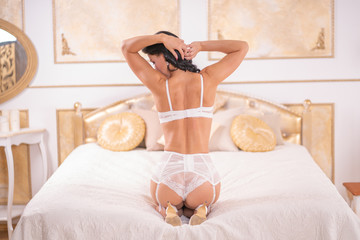 sexual caucasian slim woman wearing white romantic lingerie set with stockings and posing on the white bed in her golden bedroom