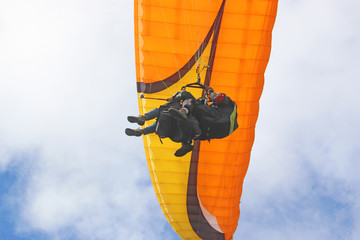 Wall Mural - Tandem paraglider flying orange wing