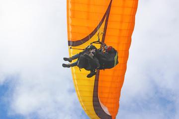 Fototapete - Tandem paraglider flying orange wing