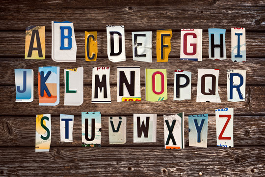 Alphabet set created with broken pieces of vintage car license plates on wooden planks background