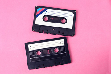 group of two audio retro vintage cassete tape 80s style on pink background