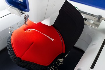 Close up picture of working embroidery machine and red cap